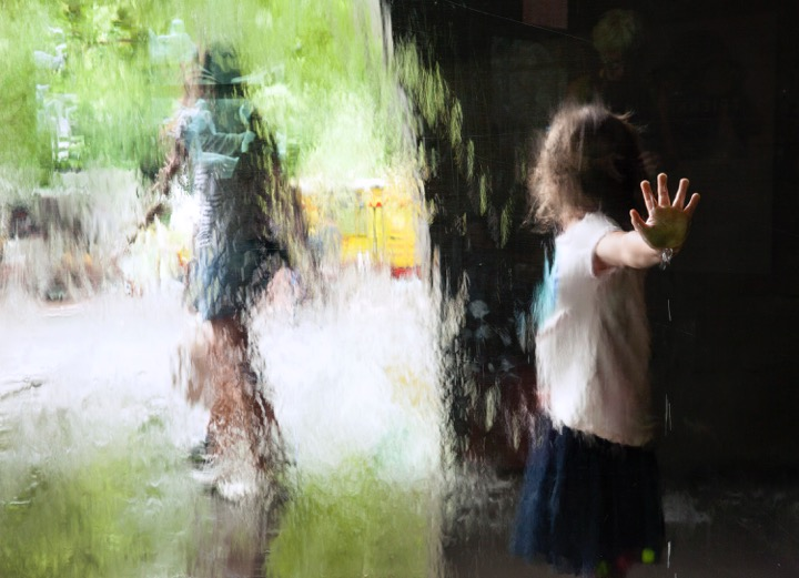 A photograph of a child pressing their hand against water falling down a window. The child's hand is in focus, the rest  of the image is blurred by the water.