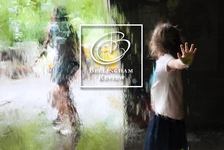 Bellingham Review issue 77 cover image: A photograph of a child pressing their hand against water falling down a window. The child's hand is in focus, the rest of the image is blurred by the water.