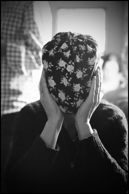 A black and white photo of a person hiding their face with a patterned object.