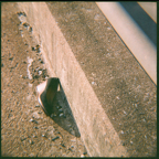 A photo of a woman's shoe leaning against concrete