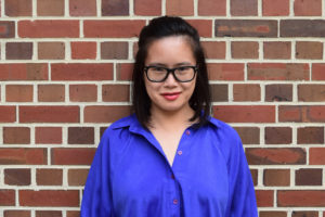 headshot: Dorothy Chan in a blue shirt standing in front of a brick wall