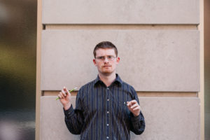 Author Photo: DJ Savarese standing in front of a tan wall with two vertical lines
